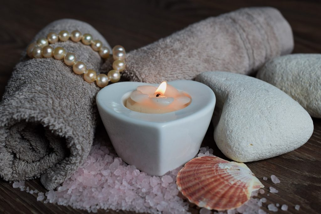 a purple towel with a heart shaped tea light candle lit, shells stones other rolled towels and pearls all around