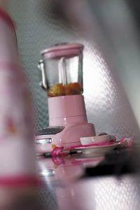 pink kitchen blender with fruit in on a grey countertop