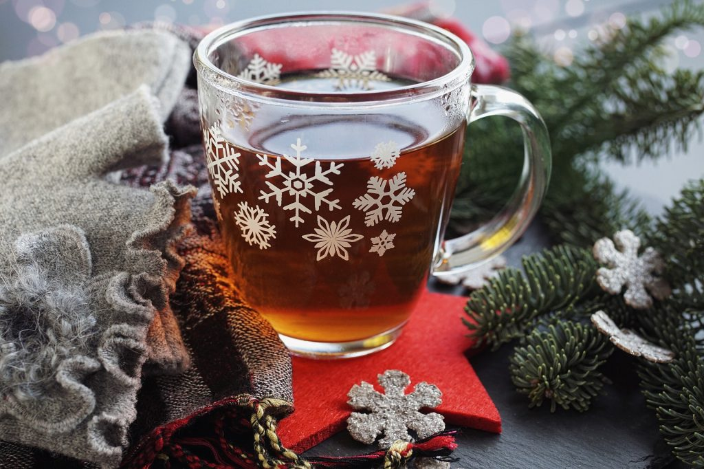 a clear glass mug with a spiced tea inside the mug is surrounded by pine tree branches and white plastic snowflakes