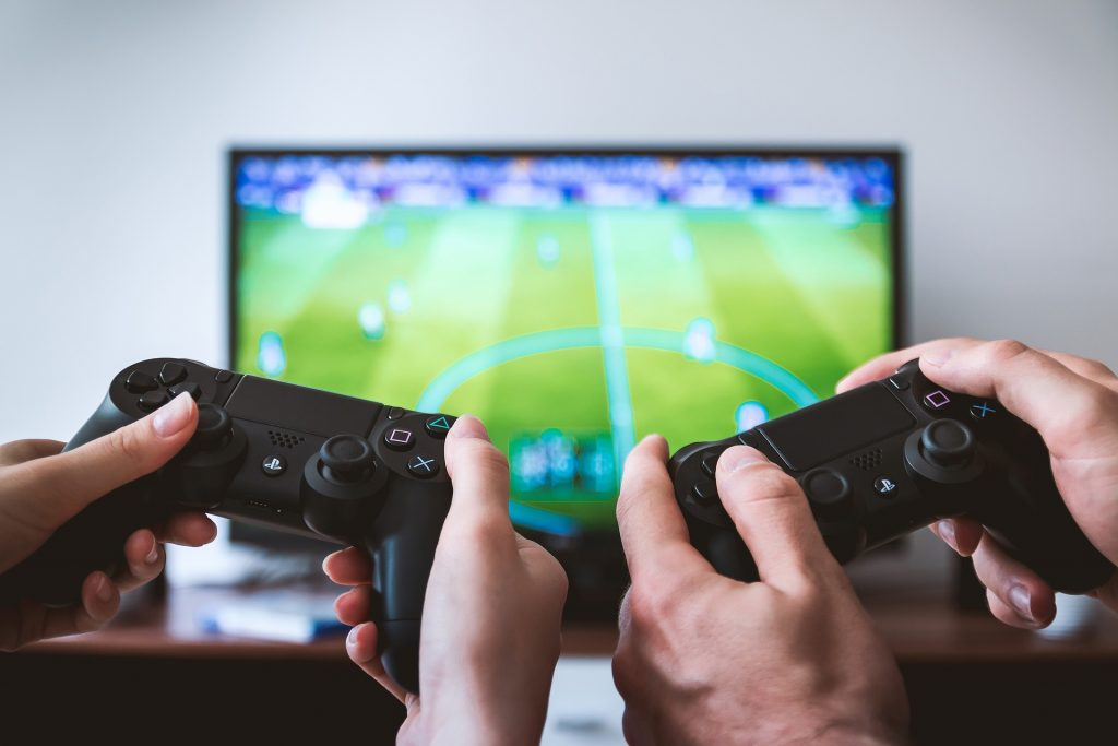 two game controllers in front of a screen