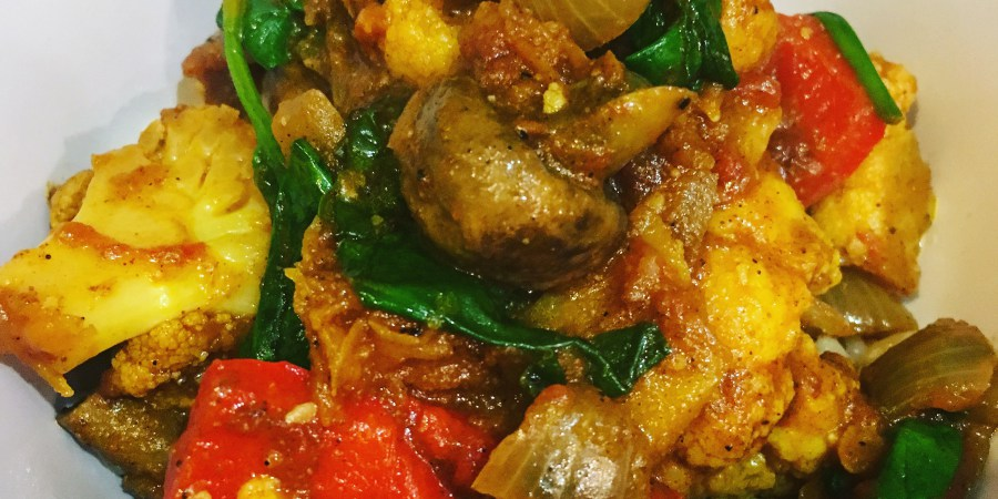 a pile of vegetables in a yellow curry sauce