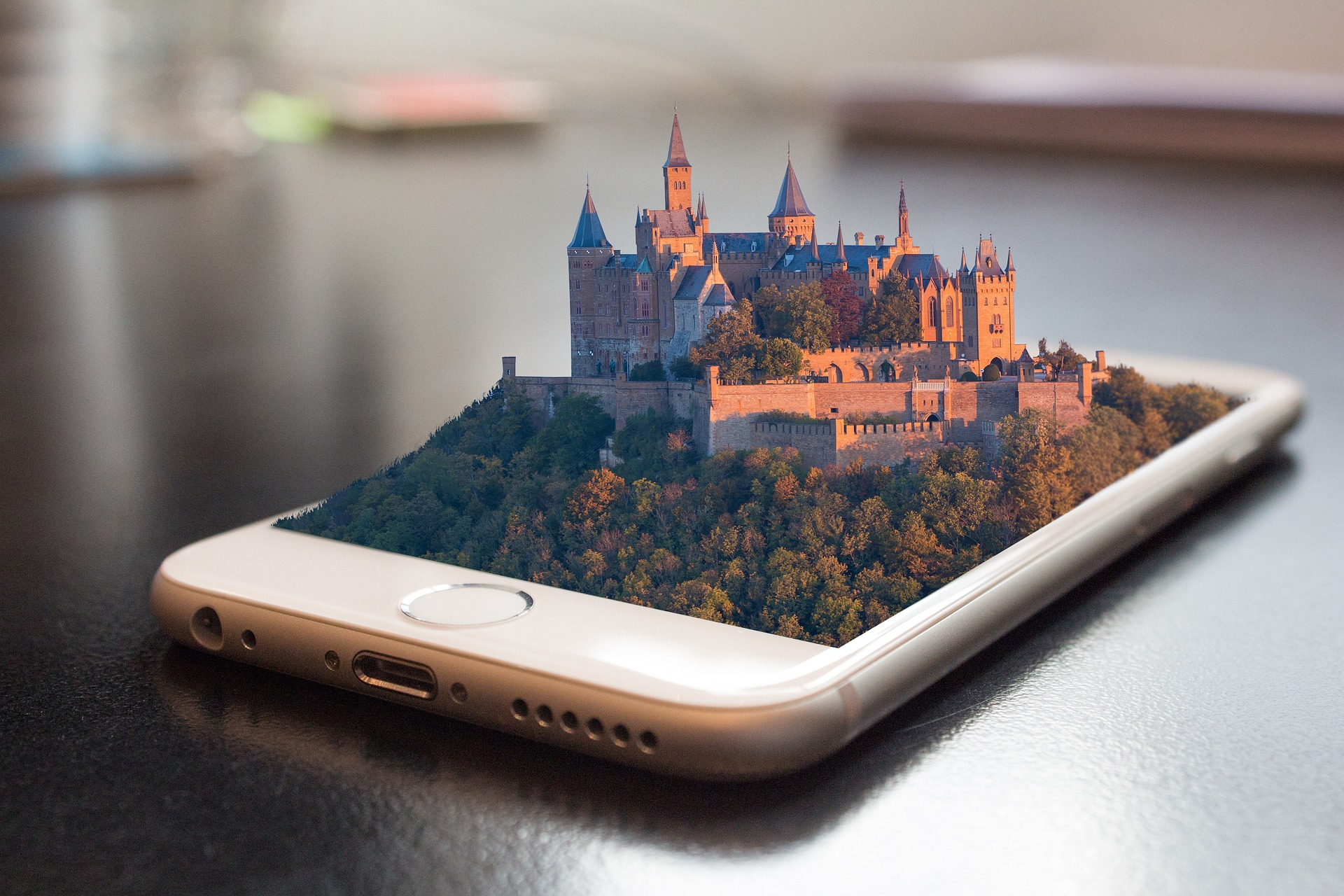 a white mobile phone on a table with a picture of a castle coming out of it that looks 4d