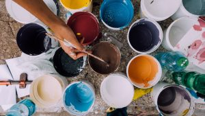 a flat lay of open paint cans in various colours with a hand stretching out over them holding a paintbrush