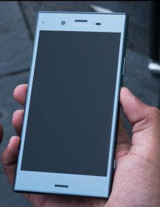 a hand holding a sony xperia xz1 compact in metallic blue screen up. the screen is black as the phone is off