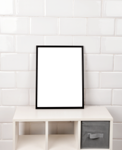 a white brick wall with a white set of shelves in front of it and on top a black picture frame with a plain white picture inside