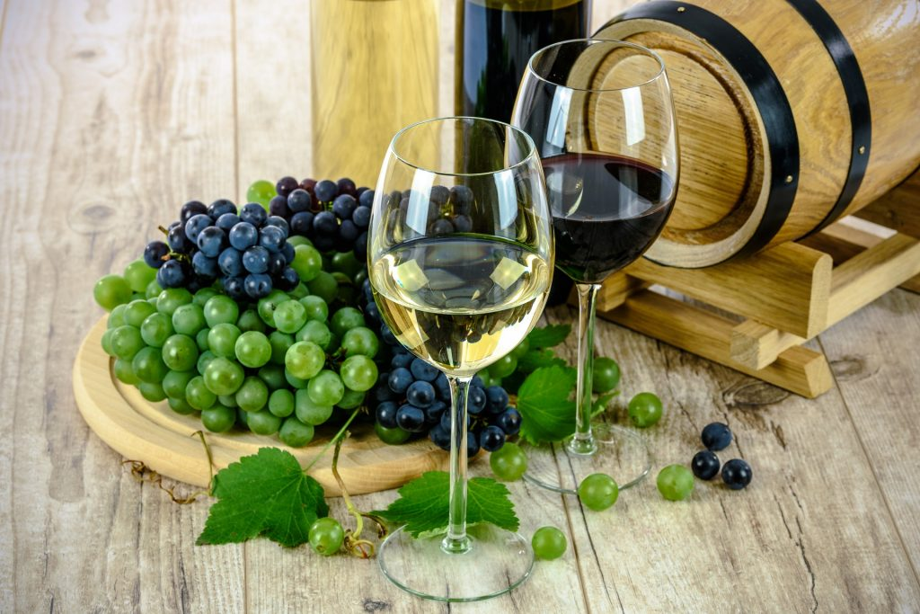 a wooden barrel with green and red grapes in front and 2 glasses one with white and one with red wine