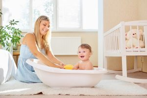 a mother bathing her baby in a yellow room in a white baby bath on the floor. both smiling at camera. room sunny