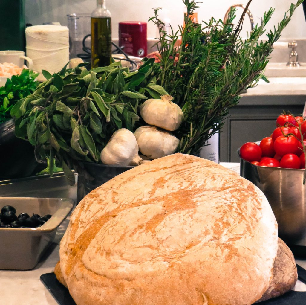 a big round load of italian bread with a bowl of red tomatoes and another bowl with fresh green herbs and garlic in and then a dish of black olives