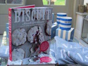 a cooking book, mugs and jumpers on a table