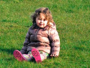 alyssa in a coat and wellies sat on grass smiling at the camera
