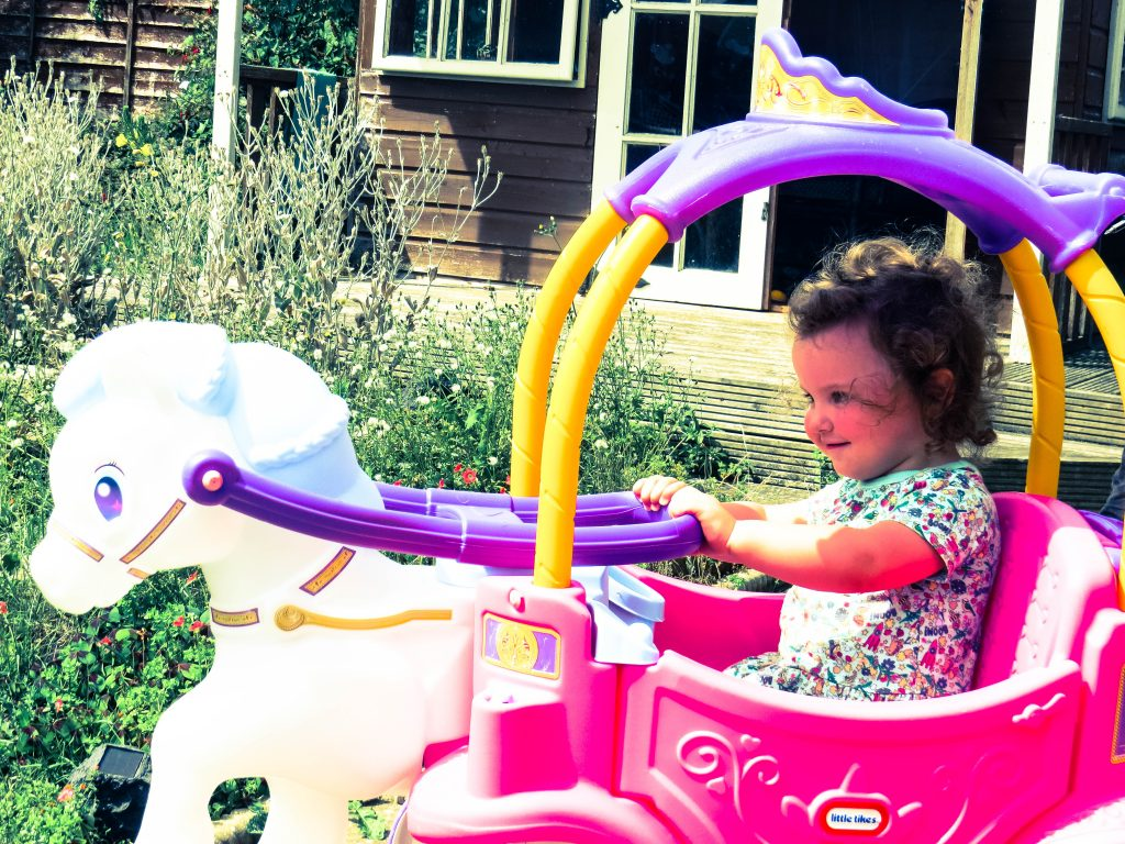 alyssa in a pink and purple plastic horse and carriage with a white horse