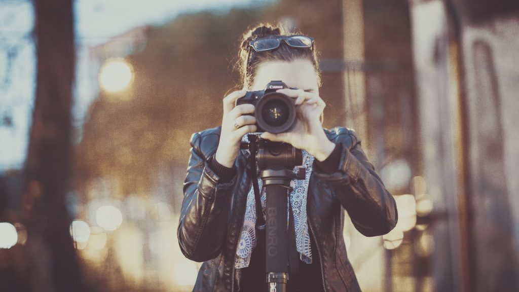 a woman in a leather jacket facing the camera holding a camera to her face. a photographer taking photos