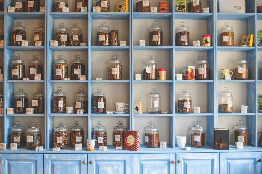 4 stacks of tall blue shelves to the ceiling with cupboards underneath and mason jars with cooking ingredients stood on each shelf