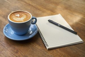 a blue cup and saucer with a coffee in on a wooden table with a blank notebook and pen next to it
