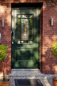 a green front door with a frosted glass panel in the middle on a red brick building with a plant either side and a doormat