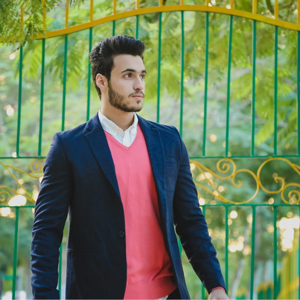 a dark haired man outside a green gate behind it is green trees. he is wearing a dark jacket and pink top