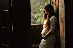 a pregnant woman holding her bump in a white dress in a dark room by an open window that has green foliage outside it