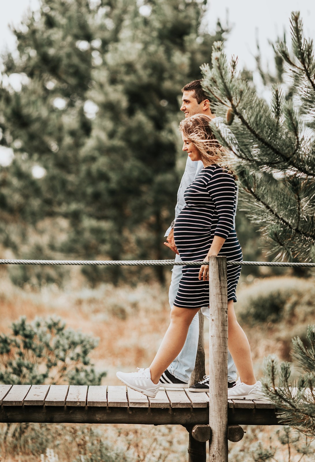 a couple walking along a wooden bridge holding hands. the woman is pregnant