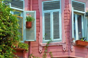 a pink house with white shuttered winders and plants around the windows
