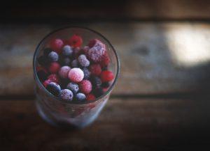 a glass full of frozen summer berries