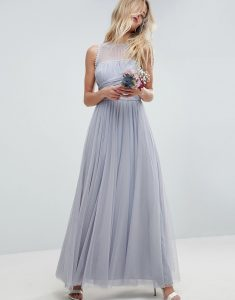 a blonde girl stood in a pale blue tulle dress holding flowers
