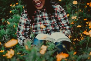 a woman in a plaid shirt sat on grass with a book and laughing