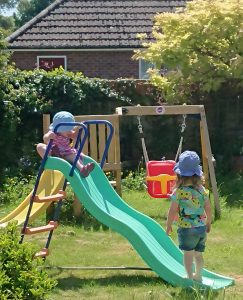 Alyssa and Lily going down the slide in the garden