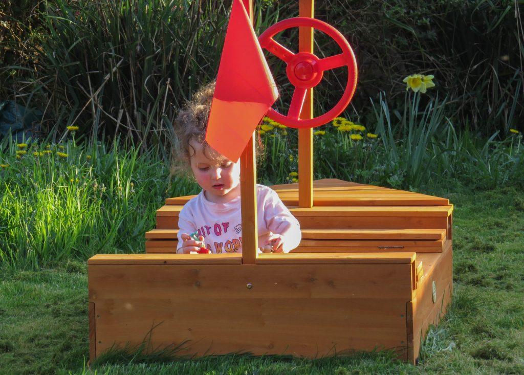 Alyssa in a wooden boat in the garden