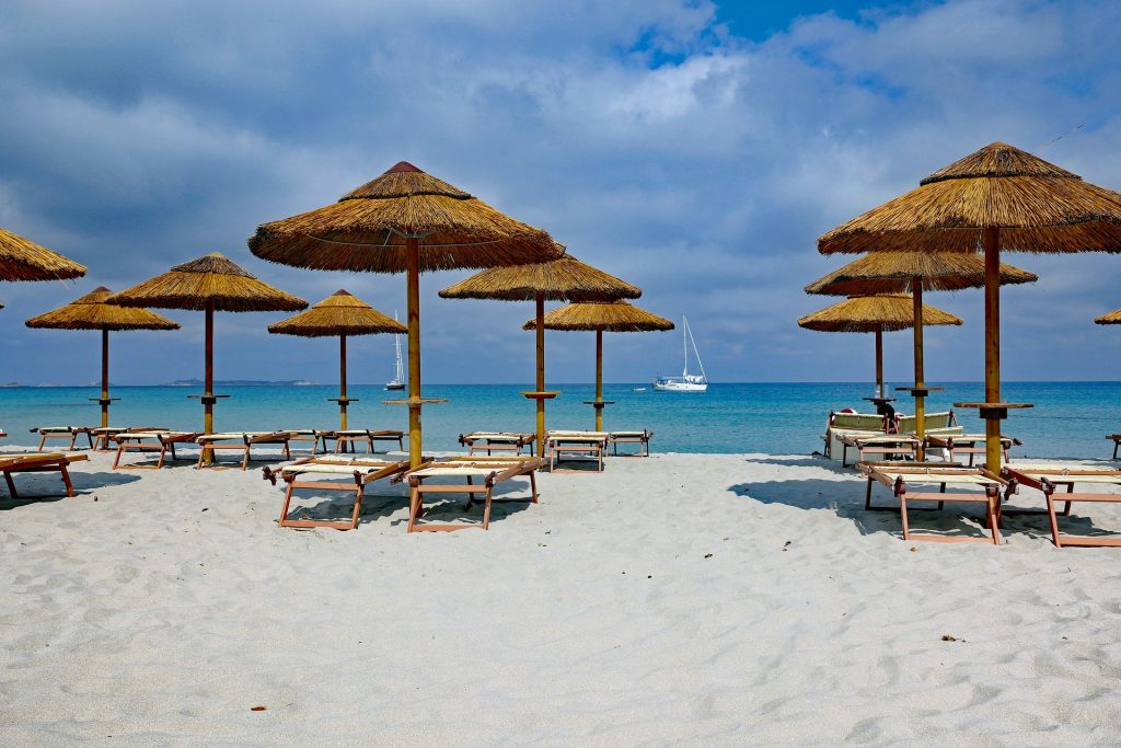 a white sand beach with palm umbrellas and sunbeds looking out to the blue sky and sea