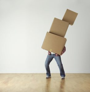 a man holding 3 boxes stacked up over him about to fall