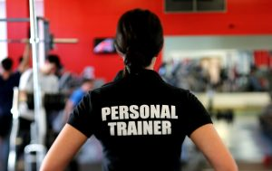 a woman with her back to the camera wearing a tshirt that says personal trainer