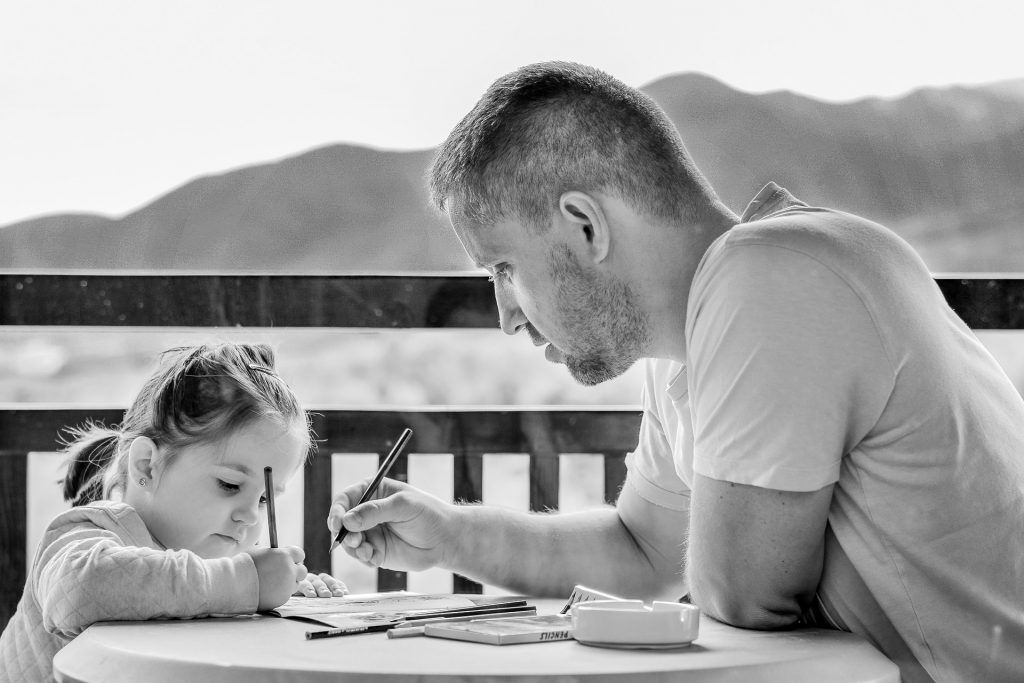 a dad sat at a table with his daughter teaching her