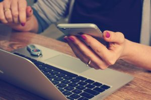 a woman at a laptop and holding a phone in one hand