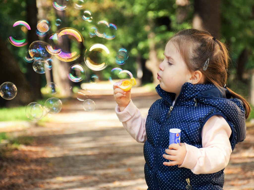 a little girl blowing bubbles in the woods