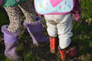 2 sets of childrens wellies in the mud