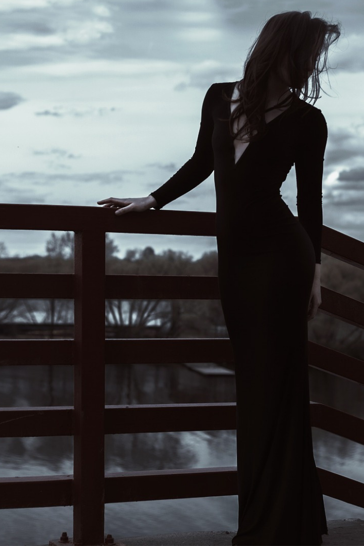 a woman in a black dress standing against a fence
