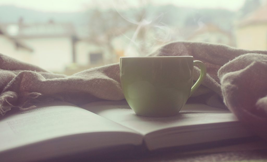 a mug of steaming coffee on a book in morning light for breakfast