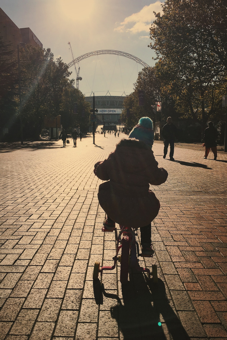 a child riding a bike down a street into the sun