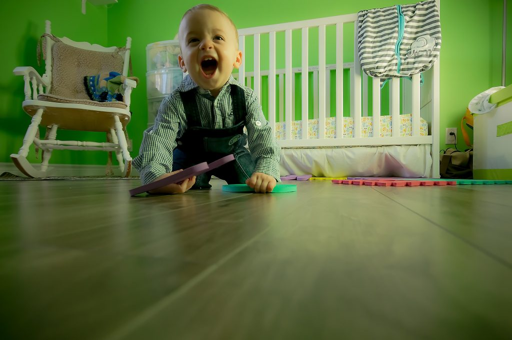 a toddler crawling on the floor smiling at the camera