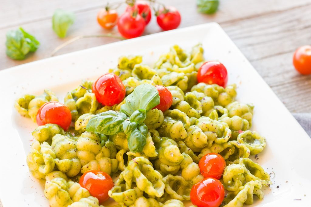 a plate of avocado basil pasta with tomatoes