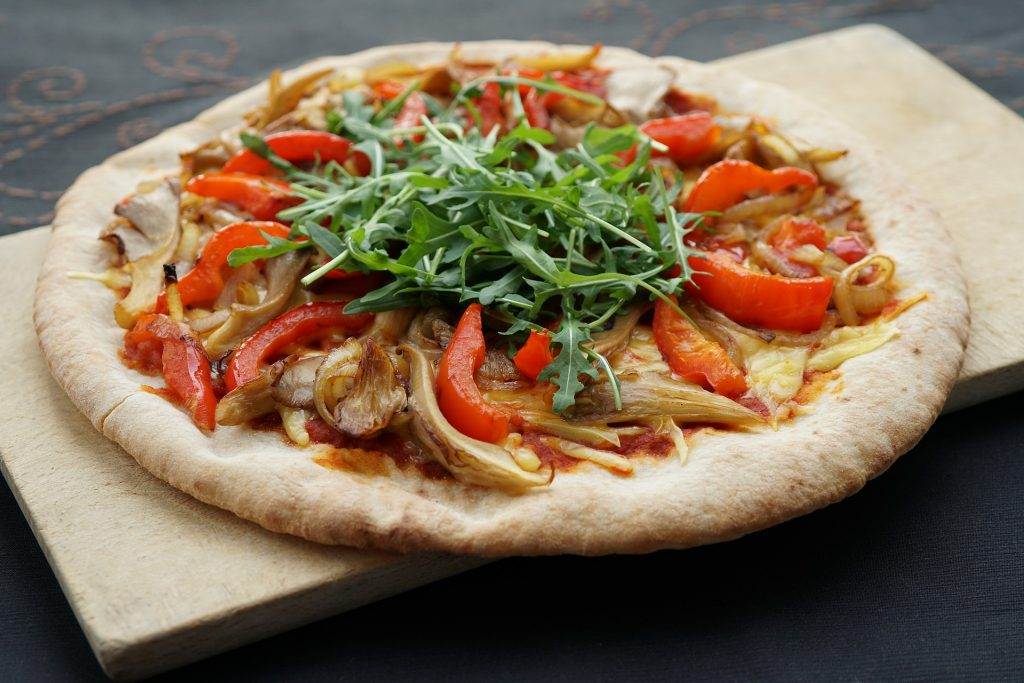 a whole pizza with onions peppers and rocket on a wooden chopping board. vegan