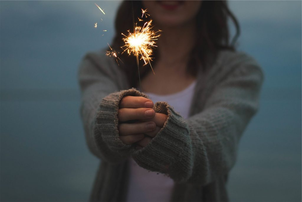a woman wearing a cardigan holding out a sparkler