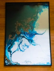black framed poster of blue gold and white swirls