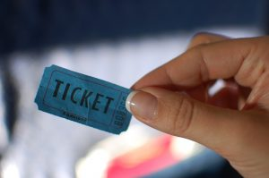 a woman's hand holding a blue ticket stub that says ticket