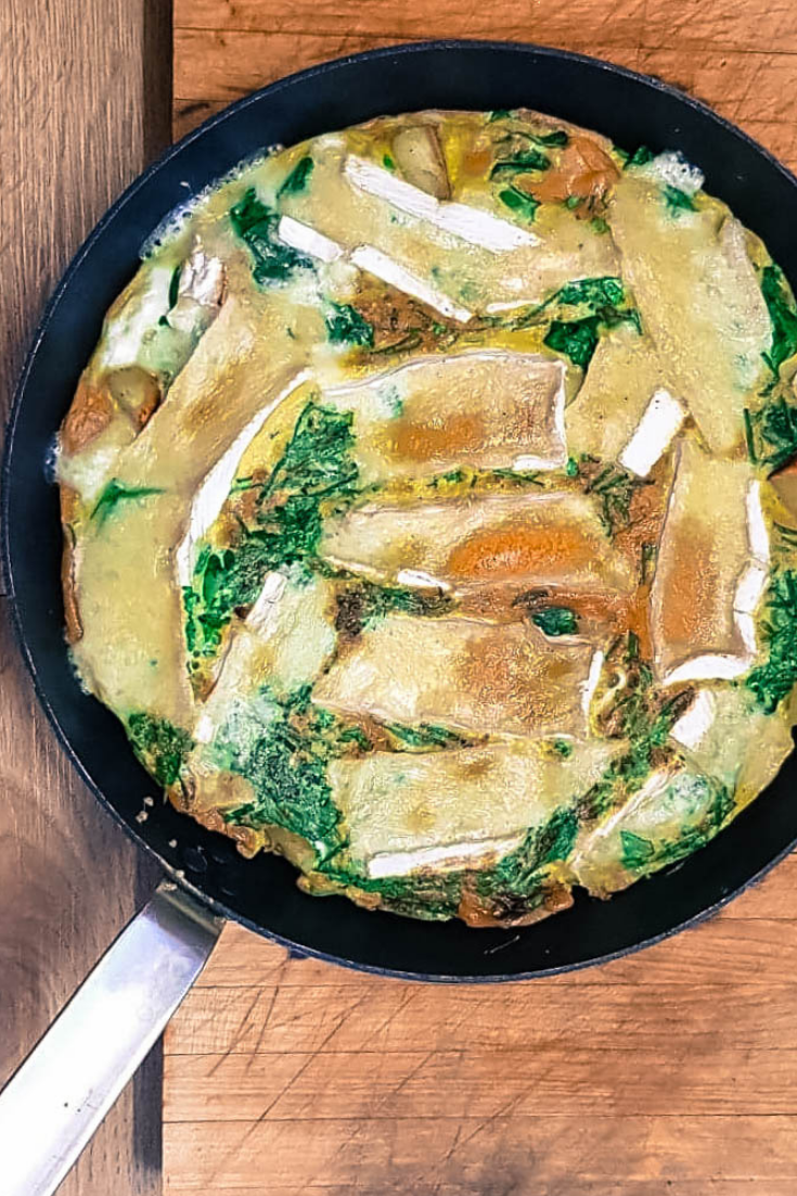 the brie and herb frittata in a skillet, cooked