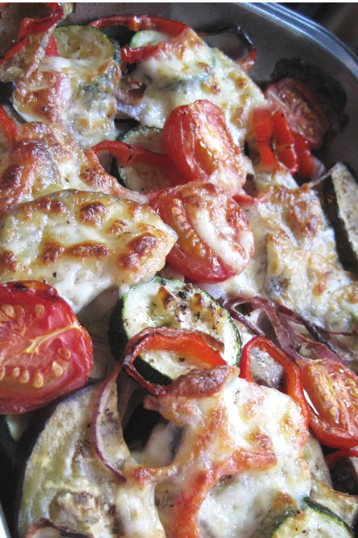 a tray of roasted vegetables with mozzarella on them
