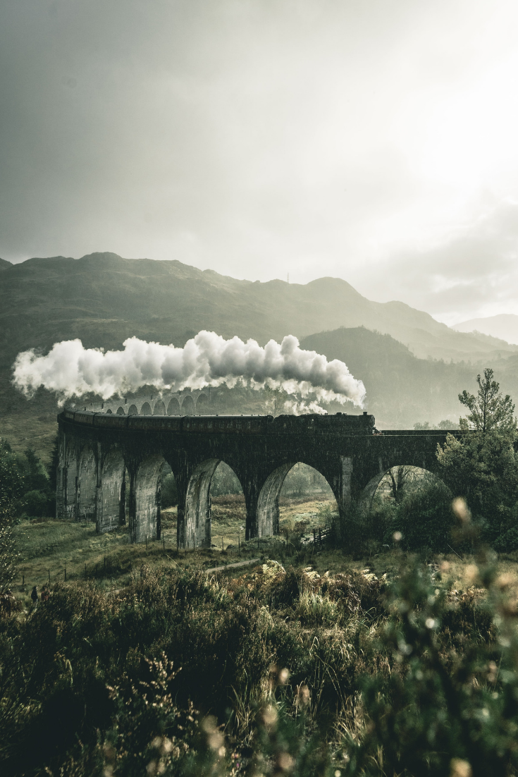 the hogwarts express moving along the arched railway bridge