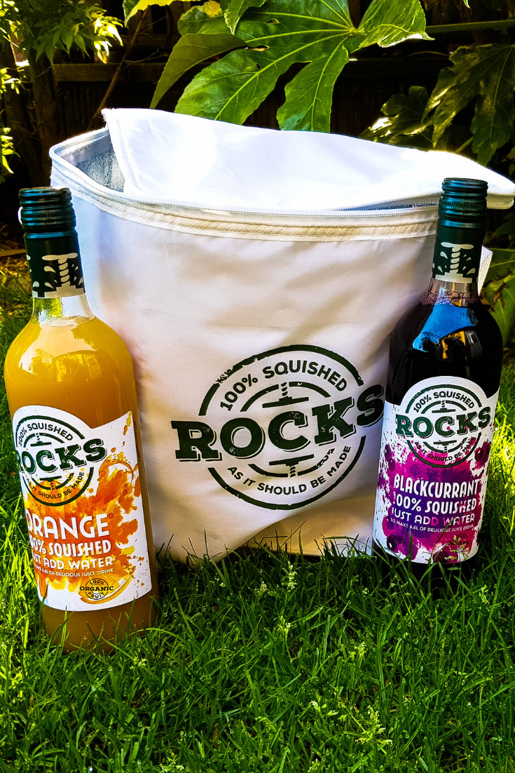 a white rocks drinks cool bag with a bottle of orange and bottle of blackcurrant drink either side