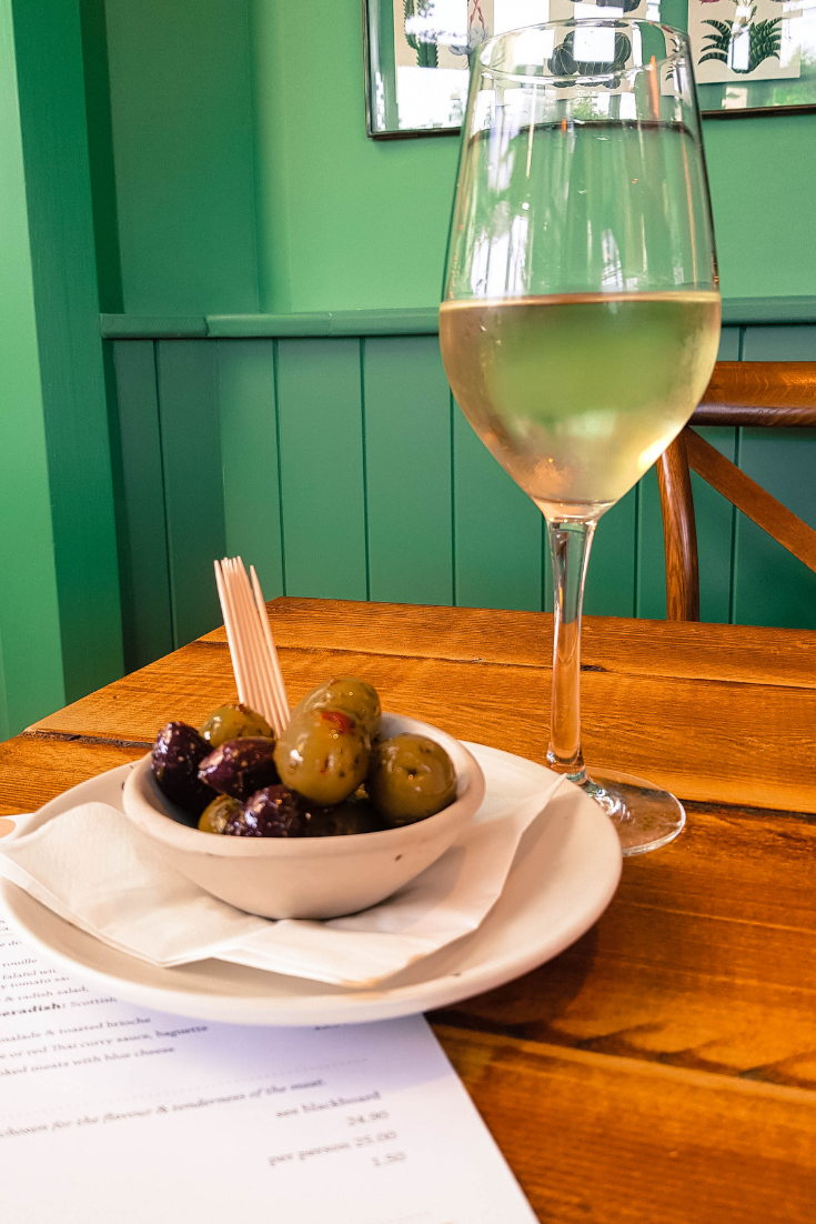 glass of white wine and a bowl of olives at the oaks highcliffe