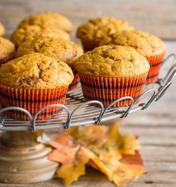apple pie muffins on a cake stand with some autumn leaves